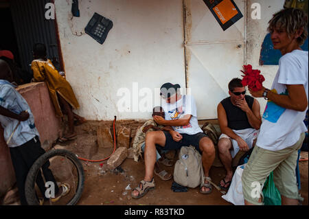 Mali, Africa. White caucasian mature volunteer enjoys playing with children in a rural village near Bamako. - Stock Image