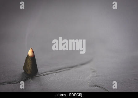 Close up of a burning Krottendorfer incense cone against grey background - Stock Image