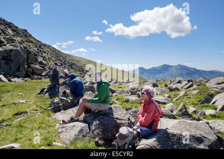 Ramblers hikers resting on rocks on Moel Siabod with view to Snowdon in mountains of Snowdonia National Park Conwy - Stock Image