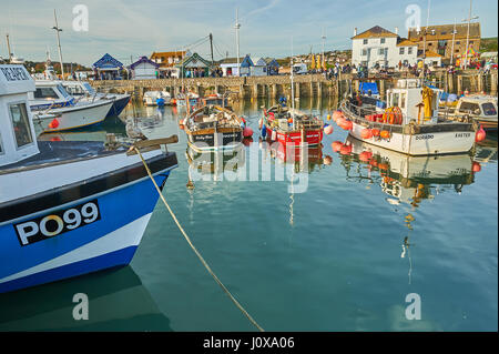 High tide, fishing boats and trawlers in the small seaside town of West Bay on Dorset's Jurassic Coast. - Stock Image