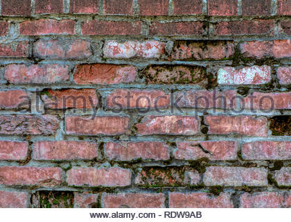 Faded red brick wall with white mortar and a few bricks missing- texture or background - Stock Image