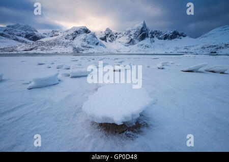 Ice on shoreline at low tide in Flakstadpollen, Flakstadøy, Lofoten Islands, Norway - Stock Image