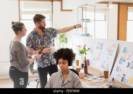 Creative designers examining bottles in office - Stock Image