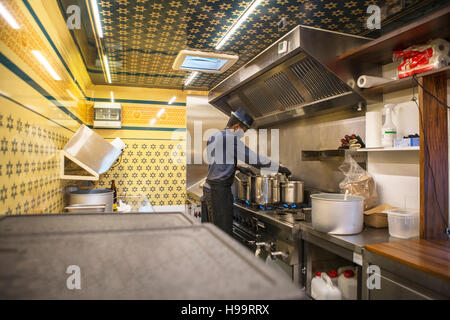 Man with hat cooking in commercial kitchen of food truck - Stock Image