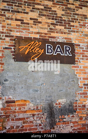 Alley Bar advertising sign on old brick wall in the entertainment district of Montgomery Alabama, USA. - Stock Image