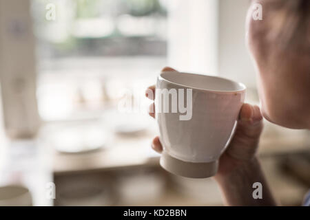 Potter holding cup - Stock Image