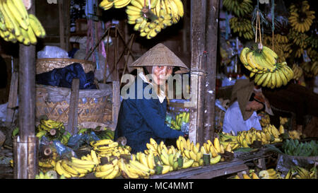 A woman in a traditional straw hat selling bananas at a local market in Vietnam. - Stock Image