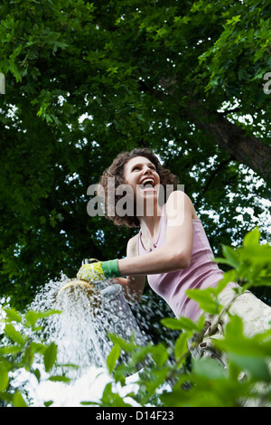 young woman watering plants in garden - Stock Image