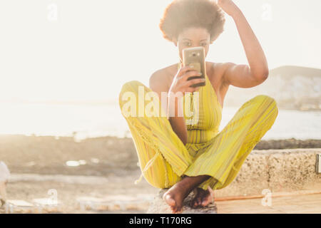 Young beautiful millennial diverse black african girl use the modern phone like a mirror to check her beauty and make up and hair - fashion woman with - Stock Image