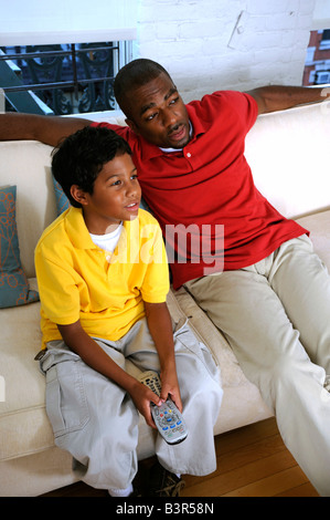 African American father and son watching TV on a couch - Stock Image
