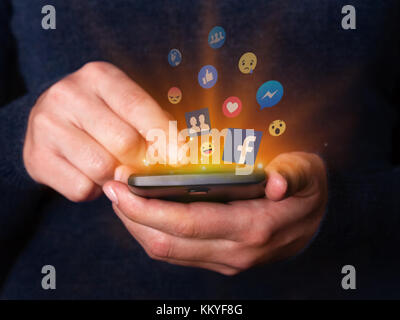 Woman hands holding using smartphone mobile cell phone Facebook social media network app Like messenger friends - Stock Image