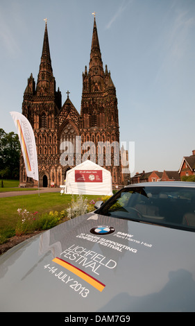 Lichfield Cathedral with banners ready for the 2013 Lichfield Festival with bonnet of BMW car in foreground. - Stock Image