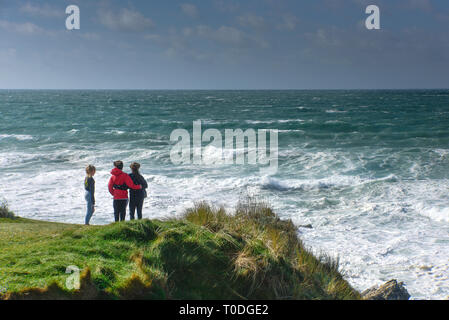 Young people looking out to sea on the rugged coastline at Little Fistral in Newquay in Cornwall. - Stock Image