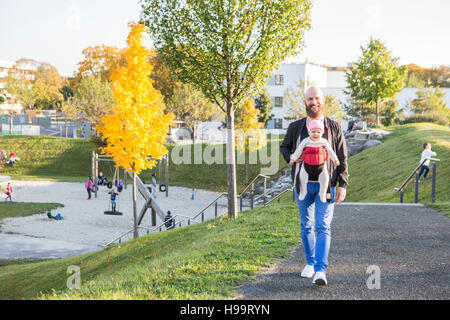 Father with baby girl in baby carrier walking in park - Stock Image