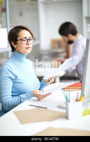 Serious accountant sitting by desk and looking through financial documents on working day - Stock Image