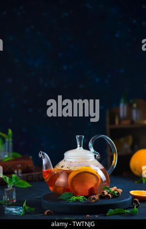 Citrus tea with cinnamon and mint leaves in a glass teapot, dark food photography with copy space. - Stock Image