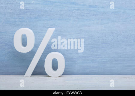 Close-up Of White Percentage Sign In Front Of Blue Wall - Stock Image