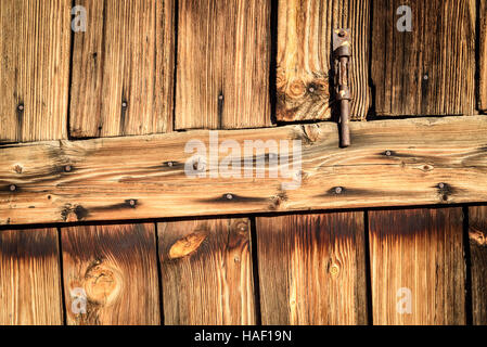 Rusty metal hinge on aged faded wood in brown. Vertical composition of fading timber and a door entrance opening. - Stock Image