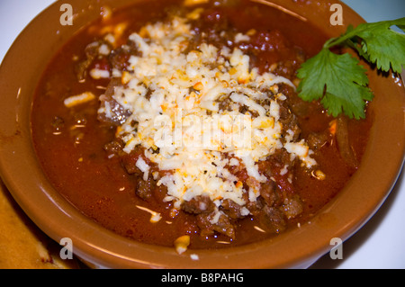 wild game venison chili brown bowl topped shredded cheese closeup food detail San Antonio Texas Dining Tex-Mex - Stock Image