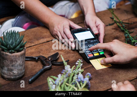 Cropped image of customer paying with credit card - Stock Image