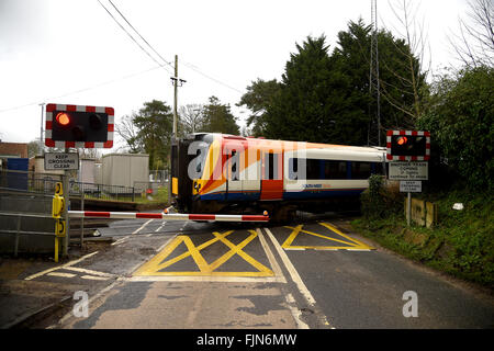 Railway level crossing with the barriers down, UK - Stock Image