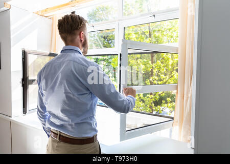 Rear View Of A Man Opening Window To Get Fresh Air At Home - Stock Image