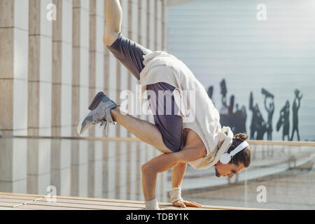 Attractive athletic man practicing yoga with maces outdoors in park next to modern building. - Stock Image