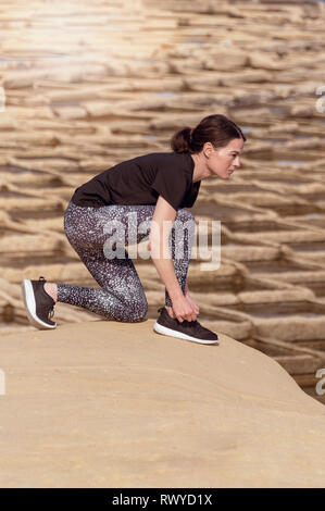 sportswoman doing up her running shoes before exercising outside in the sun - Stock Image