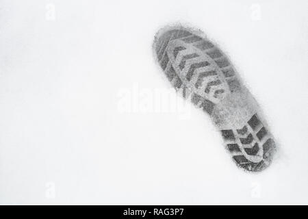 one right foot shoe print on snow, top view, copy space, cloudy, no sunshine - Stock Image