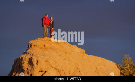 Low angle view of couple standing on remote boulder under sunset sky - Stock Image