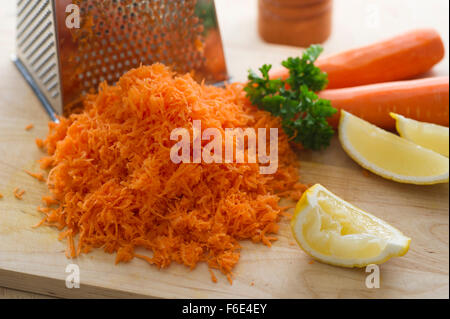 Grated carrot, sliced lemon and parsley. - Stock Image