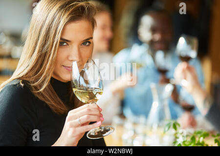 Young woman with friends at a wine tasting or tasting smells by the glass - Stock Image