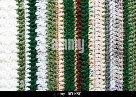 Closeup of an afghan crocheted from acrylic yarn with colors of the changing seasons, from winter into spring. - Stock Image