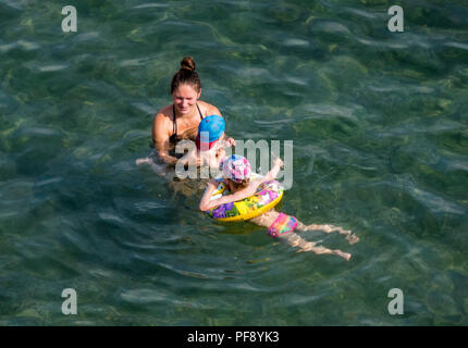 a mother in the sea or water with her children teaching the kids to swim on a summers warm day. family cooling off in the Ionian sea on corfu. - Stock Image