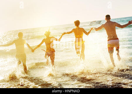 Friends fun beach susnet run - Stock Image