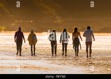 A group of people walking across Fistral Beach in evening light. - Stock Image