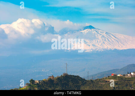 Smoking snow-capped Mount Etna volcano at sunrise, as seen from Taormina, Sicily - Stock Image
