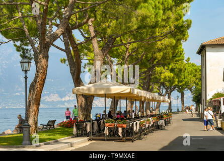 TORRI DEL BENACO, LAKE GARDA, ITALY - SEPTEMBER 2018: Outdoor dining area at a restaurant on the promenade on the edge of Lake Garda - Stock Image