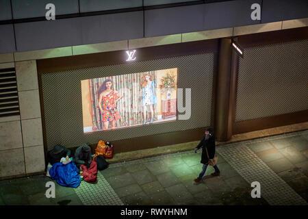 Homeless beggars outside louis vuitton designer store in Selfridges  Manchester city centre - Stock Image