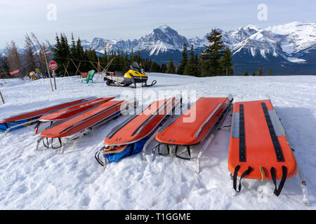 Rows of ski patrol toboggans or rescue sleds lie on snow on mountain ski resort. Also known as akia or emergency rescue sledg, it is used by mountain  - Stock Image