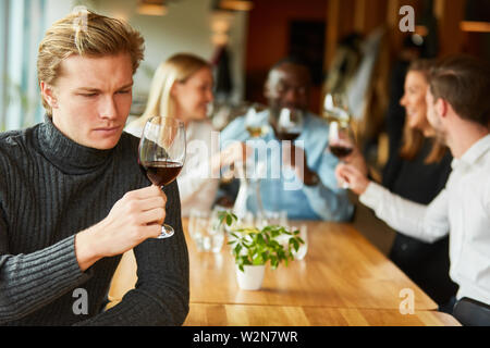 Young man at a wine tasting or tasting critically examines a glass of red wine - Stock Image