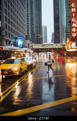 Chicago, United States. 14th Jun,  2017. A woman hails a taxi in the middle of the street as she attempts to get - Stock Image