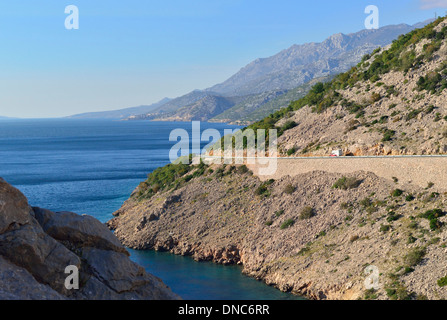 Coastal  hugging road below the cliffs of the escarpment  that stretches  the length of croatia - Stock Image