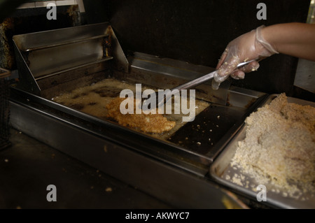 A cook deep frying chicken breast. - Stock Image