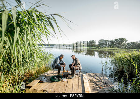 Two fishermen relaxing during the picnic on the beautiful wooden pier with green reed on the lake in the morning - Stock Image
