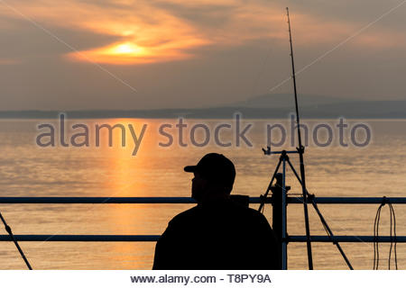 Morecambe, Lancashire, UK, 14 May 2019, UK Weather. Fishermen on the Stone Jetty at Morecambe as the sun sets over Morecambe Bay. With an incoming tide, the fishermen are hoping to catch Smooth-hound, a shallow water shark species which come into upper reaches of the Bay on a rising tide. Another day of unbroken sunshine is forecast for Wednesday. Credit: Keith Douglas News/Alamy LiveNews - Stock Image
