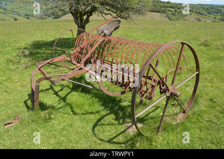 Hay rake retired to a field on Exmoor, converted from horse drawn to tractor powered. Exford, Somerset UK - Stock Image