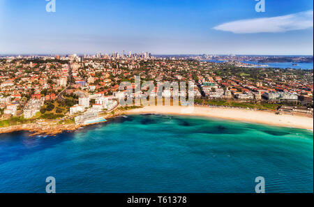 Waterfront of famous Bondi beach in Sydney from emerald waters of Pacific ocean to distant city CBD cityscape on the horizon on a sunny day. - Stock Image