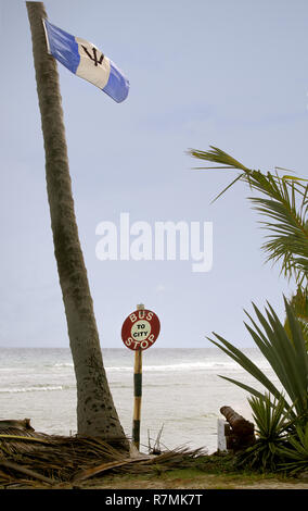An old bus stop has been placed next to the sea along with two rusted cannons, (only one visible), and the barbadian flag mounted on a tree - Stock Image