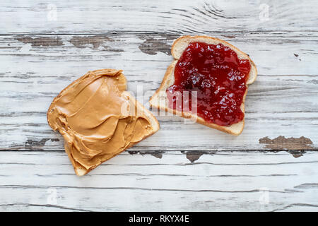 Top view of open face homemade peanut butter and strawberry Jelly sandwich on oat bread, over a white rustic wooden table / background. - Stock Image